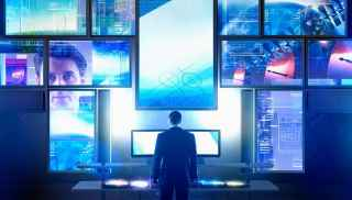Man standing in front of computer technology